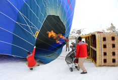 Ground crew torch the flame and heat up the balloon to inflate Stock Images