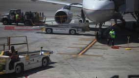 Ground crew working on unloading an airplane. Unrecognized airplane being unloaded at Houston International Airport by ground crew on August 2nd 2016 in Houston stock footage