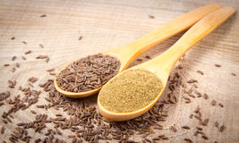 Ground cumin in a spoon and whole cumin. On the wooden background Stock Photo