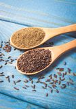 Ground cumin in a spoon and whole cumin on the wooden background. Close up on ground cumin in a spoon and whole cumin. Blue wooden background Stock Photos