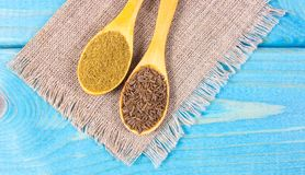 Ground cumin in a spoon and whole cumin on the wooden background. Close up on ground cumin in a spoon and whole cumin. Blue wooden background Stock Photography