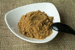 Ground cumin. In white plate with black spoon royalty free stock photos