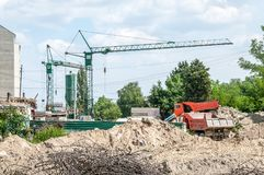 Ground excavation site with heavy tipper trucks and construction cranes on the new residential building terrain preparation, with royalty free stock image