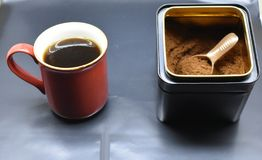 Ground Filter Coffee and a cup of coffee. Ground filter coffee and coffee in the cup brewed next to the filter royalty free stock photo