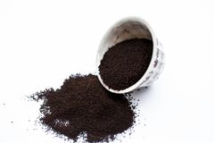 Ground finely powdered dried tea leaves from Assam with mint or peppermint leaves in a bowl isolated on white.