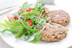 Ground fish patty with arugula tomato salad Royalty Free Stock Images