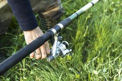 Ground fishing. Angler`s hand adjusts the tension of the fishing line with the reel. Ground fishing. The angler`s hand adjusts the tension of the fishing line royalty free stock photography