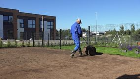 Ground harden works after lawn seeding. Static shot. Ground harden works after lawn seeding. Man Hard Working In Private House Yard with Soil Roller. Static shot stock video