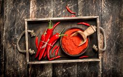Ground hot chili pepper in a bowl. On a wooden background stock photos