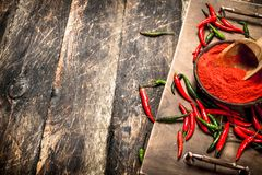 Ground hot chili pepper in a bowl. On a wooden background stock photography