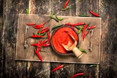 Ground hot chili pepper in a bowl. On a wooden background royalty free stock image