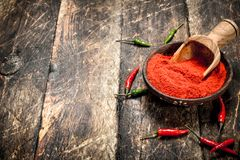 Ground hot pepper in a bowl with a scoop. On a wooden background royalty free stock images