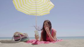 Ground level view of woman using phone at beach. Ground level view of cute young woman on pink blanket under yellow umbrella with bag using phone at beach stock video footage