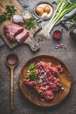 Ground meat in plate with cooking spoon with ingredients on rustic kitchen table background. Top view Stock Image