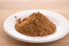 Ground nutmeg. Herb in white plate stock photo
