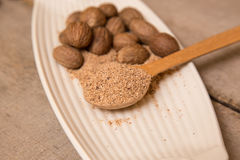 Ground nutmeg spices in a ceramic plate Royalty Free Stock Image