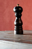 Ground pepper shaker. Over a rough brown table stock images