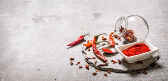 Ground red Chili pepper in a bowl and spoon on a stone stand. Royalty Free Stock Images