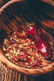 Ground red chili pepper in wooden bowl. Flakes of ground red chili pepper in wooden bowl stock image