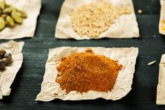 Ground red pepper among other spices on a black table.  stock photography