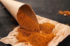 Ground red pepper in a paper bag on a piece of paper.  royalty free stock photos