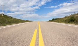 A ground shot of paved highway going up hill into the distance Royalty Free Stock Images