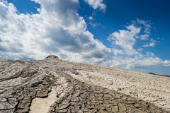 Ground and sky. Landscape produced by mud volcano with beautiful blue sky with white clouds as background stock image