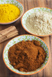 Ground Spices in Bowls with Cinnamon Sticks stock photo