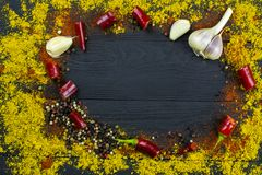 Ground spices, garlic and pepper on black wooden background. Space for text. Food background. Ground spices, garlic and pepper on black wooden background. Copy royalty free stock photography