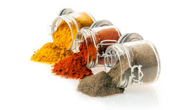 Ground spices spilling from glass jars Royalty Free Stock Image