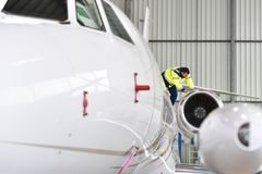 Ground staff at the airport checks the technology and safety of. A jet in the hangar Stock Images
