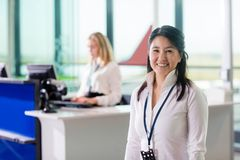 Ground Staff Smiling While Colleague Working At Airport Receptio. Portrait of mid adult ground staff smiling while colleague working at reception in airport Royalty Free Stock Photos