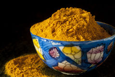 Ground Turmeric in Painted Bone China Bowl. Against a Black Background stock photography