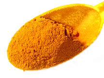 Ground turmeric on spoon over white background Royalty Free Stock Photography