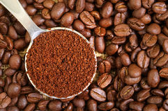 Ground and Whole Coffee Beans. Ground Coffee in Measuring Spoon on Whole Coffee Beans royalty free stock photo