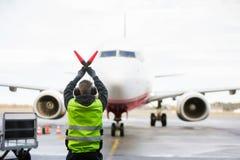 Ground Worker Signaling To Airplane On Runway. Rear view of ground worker signaling to airplane on wet runway stock photo
