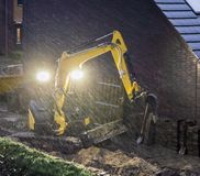 Ground worker working at night in bad rainy weather, constructing a garden in the evening. A ground worker working at night in bad rainy weather, constructing a royalty free stock photo