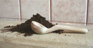Grounded coffe. E and a spoon on a brown desk Stock Image