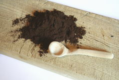Grounded coffe. E and a spoon on a brown desk Royalty Free Stock Photography
