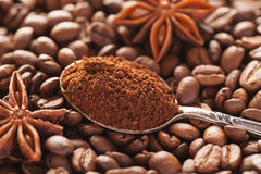 Grounded coffee in silver spoon above coffe beans Stock Photo