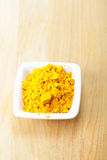 Grounded saffron spice in white dish on wood Royalty Free Stock Image