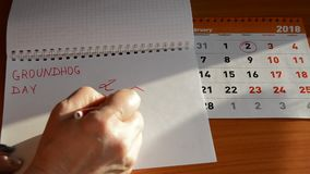Groundhog day on the calendar, a woman writing in a notebook 2 February.  stock video