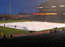 Grounds crew uses tarp to cover infield to save it Royalty Free Stock Image