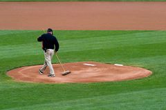 Groundskeeper Pitchers Mound. A groundskeeper preparing the pitchers mound for a game Stock Photos