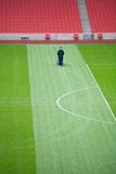 Groundsman working in stadium. Lone groundsman cuts the grass on a large football pitch Royalty Free Stock Images