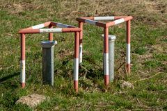 Groundwater measuring points with steel protection tube, end cap with hex locking and red and white concreted protection triangle. Drill royalty free stock photo