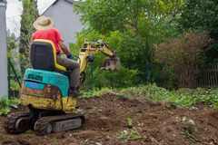Groundwork with a mini digger. Smoothing the terrain Royalty Free Stock Photos
