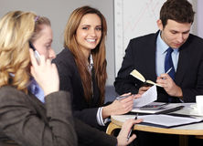 Group of 3 businesspeople sitting at table Stock Photo