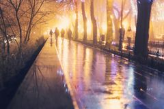 Group of abstract people walking down the rainy boulevard. Group of abstract people walking down the boulevard in Odessa city after rain. Atmospheric shot with royalty free stock photos