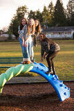 Group of active children playing outside at school playground. Group of young girl friends with cultural diversity Royalty Free Stock Photography